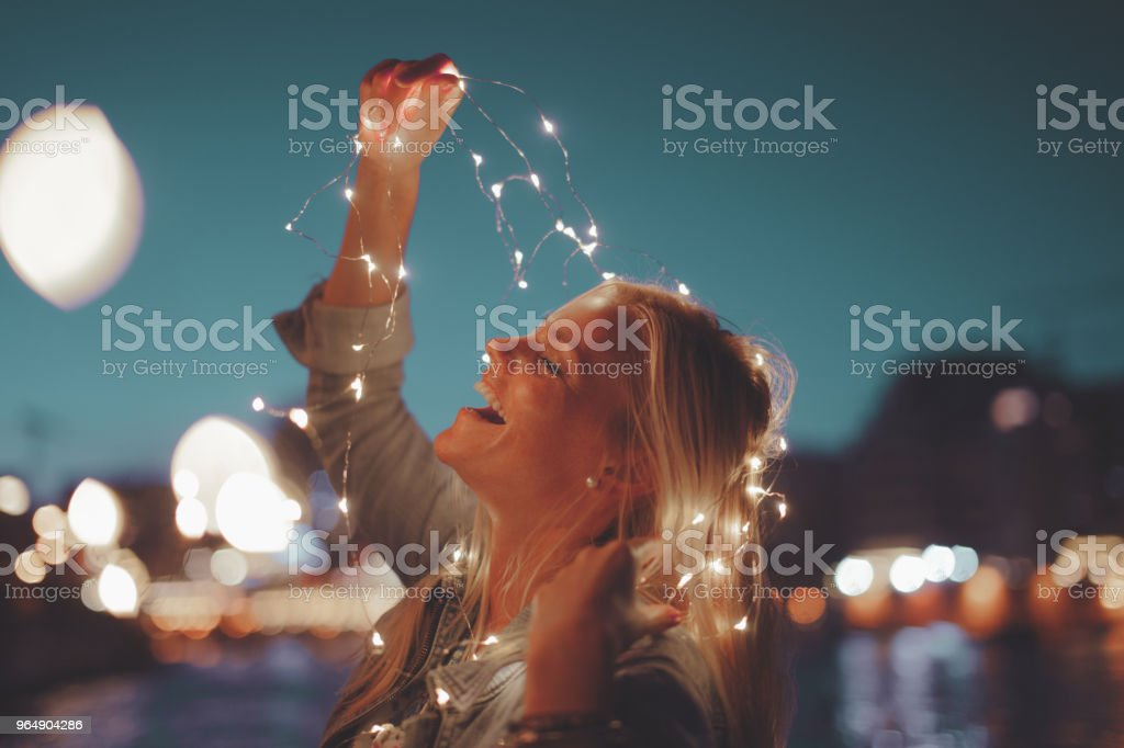 Happy young blonde woman garland fairy lights royalty-free stock photo