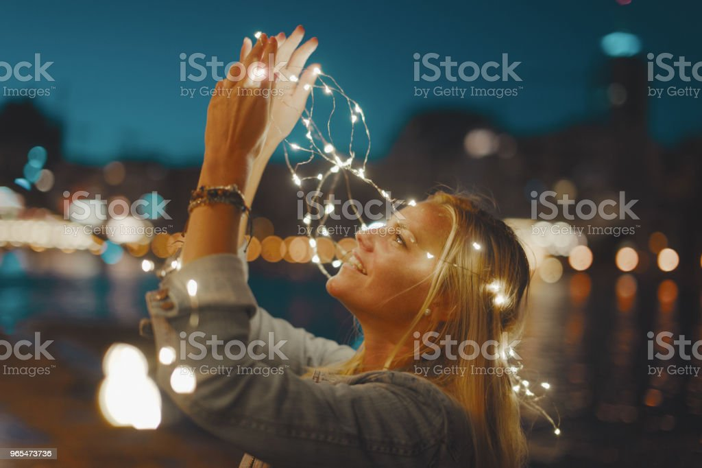 Happy young blonde woman with garland fairy lights have fun in city at night stock photo