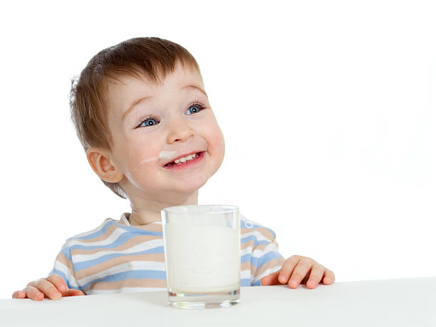 A happy young boy drinking a glass of milk stock photo