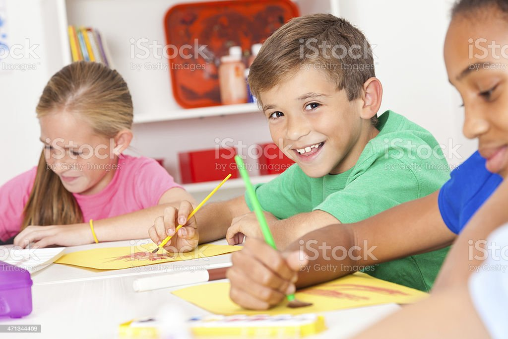 Happy young boy in his art class stock photo