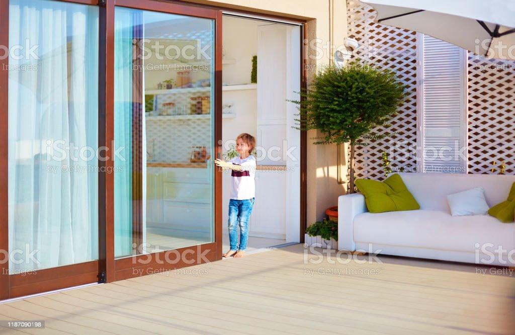 glücklicher kleiner Junge, Kind öffnet die Schiebetür auf dem Dach Terrasse Bereich zu Hause - Lizenzfrei Außenaufnahme von Gebäuden Stock-Foto