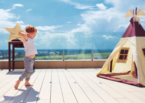 happy young boy, kid playing near the textile wigwam tent on the summer patio stock photo