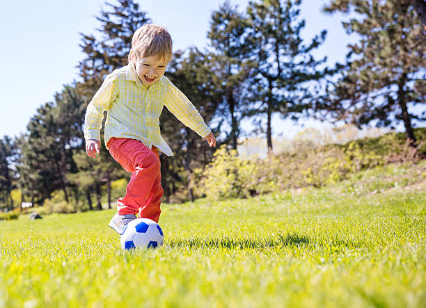 Happy young boy playing football stock photo