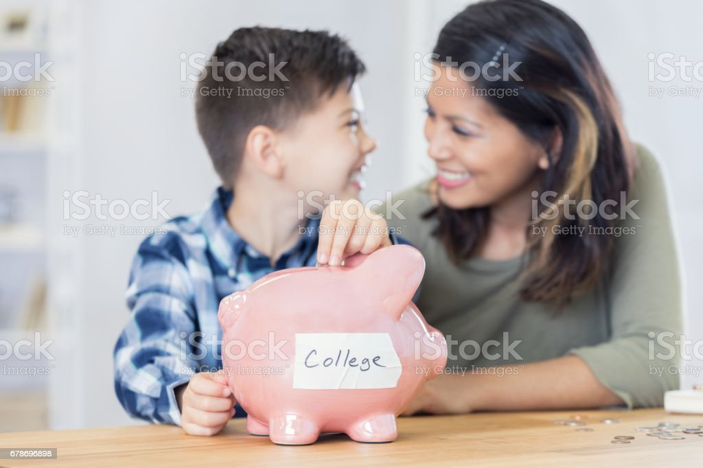 Happy young boy saves for college stock photo