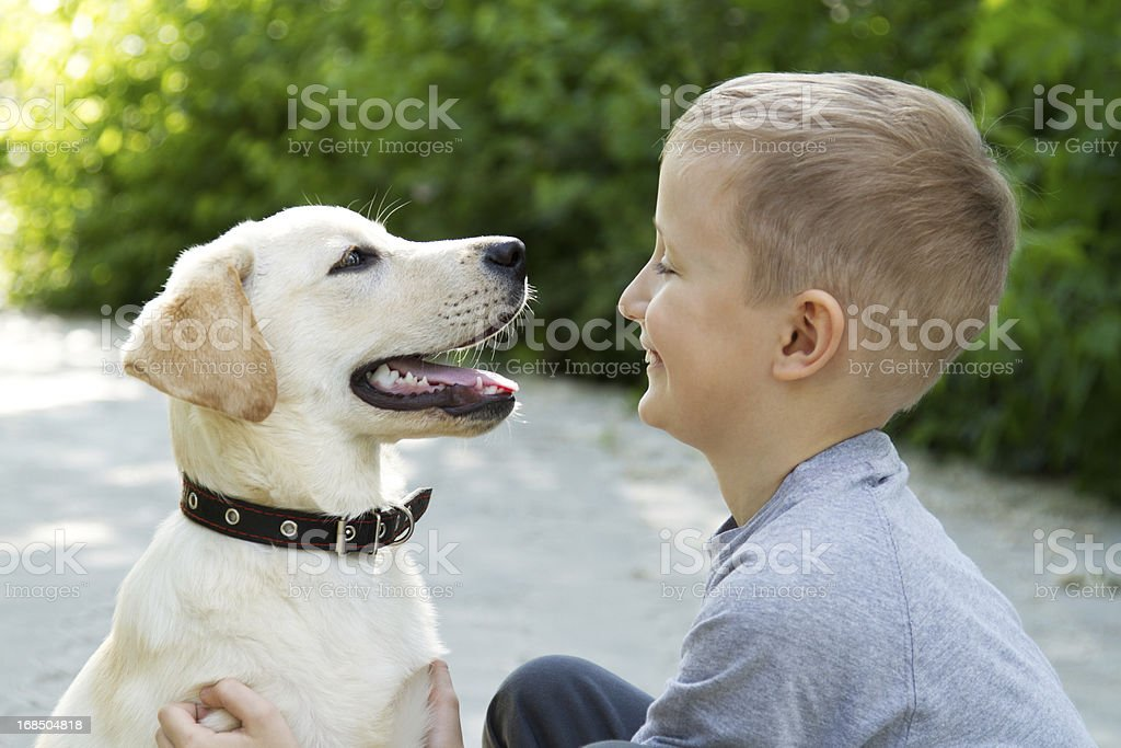 Happy young boy sitting with an excited dog with mouth open stock photo