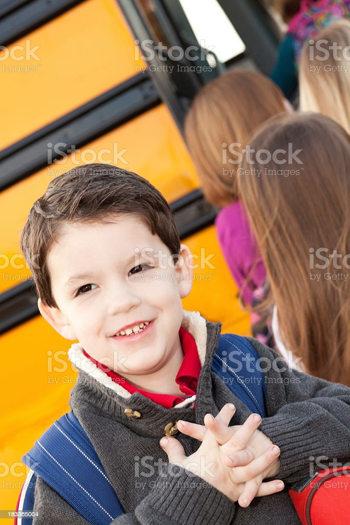 Happy Young Boy Waiting To Board School Bus With Students royalty-free stock photo