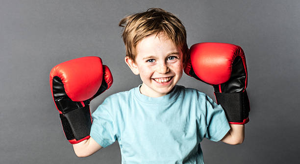 happy young boy with freckles holding big boxing gloves stock photo