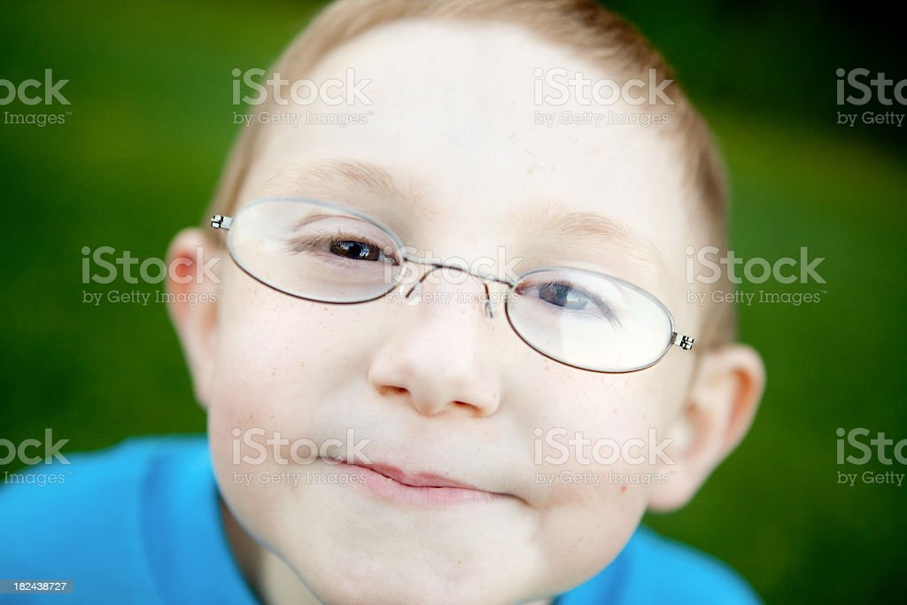 Happy Young Boy with Glasses Smiling Outside stock photo