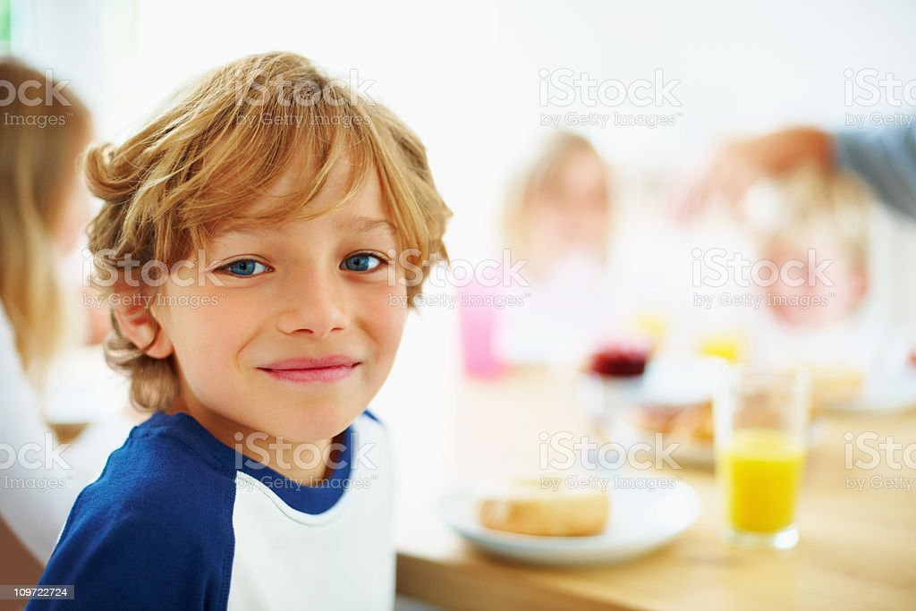 Happy young boy with his family having breakfast royalty-free stock photo
