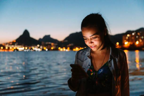 Happy young Brazilian woman using smartphone outdoors at Rio de Janeiro Happy young Brazilian woman using smartphone outdoors at Rio de Janeiro lagoa rio de janeiro stock pictures, royalty-free photos & images