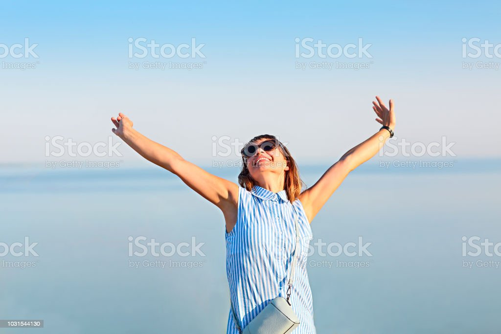 Happy young brunette woman open her arms to the sky and sea stock photo