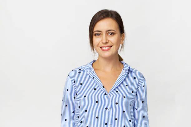 Glückliche junge Brünette Frau trägt blaues Hemd lächelnd Porträt vor weißem Hintergrund – Foto