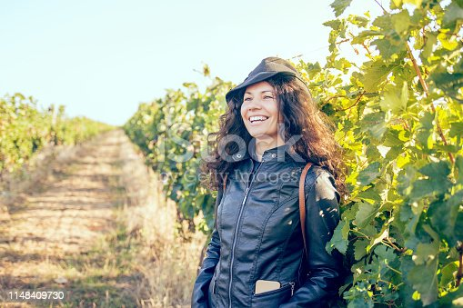 happy young brunette woman winegrower inspecting grape vines in vineyard outdoors in autumn.