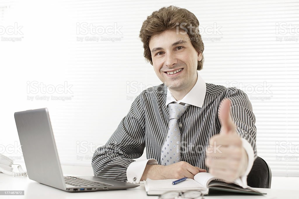 Happy young business man holding his thumbs up royalty-free stock photo