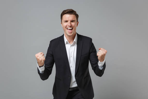 Happy young business man in classic black suit shirt posing isolated on grey wall background studio portrait. Achievement career wealth business concept. Mock up copy space. Doing winner gesture. stock photo