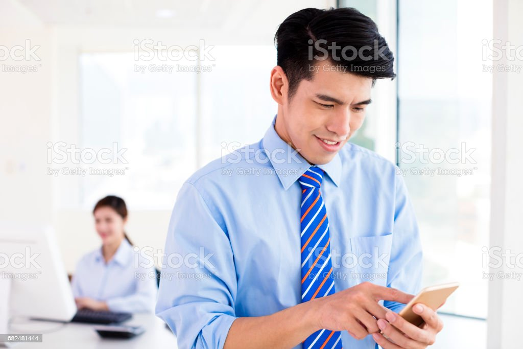 Happy young business man looking at  smart phone royalty-free stock photo