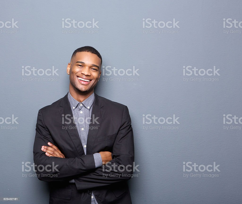 Happy young business man smiling with arms crossed stock photo