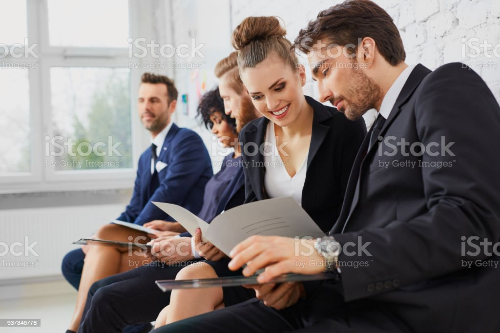 Happy young business people talking before job interview, assessment or test, exam at university stock photo