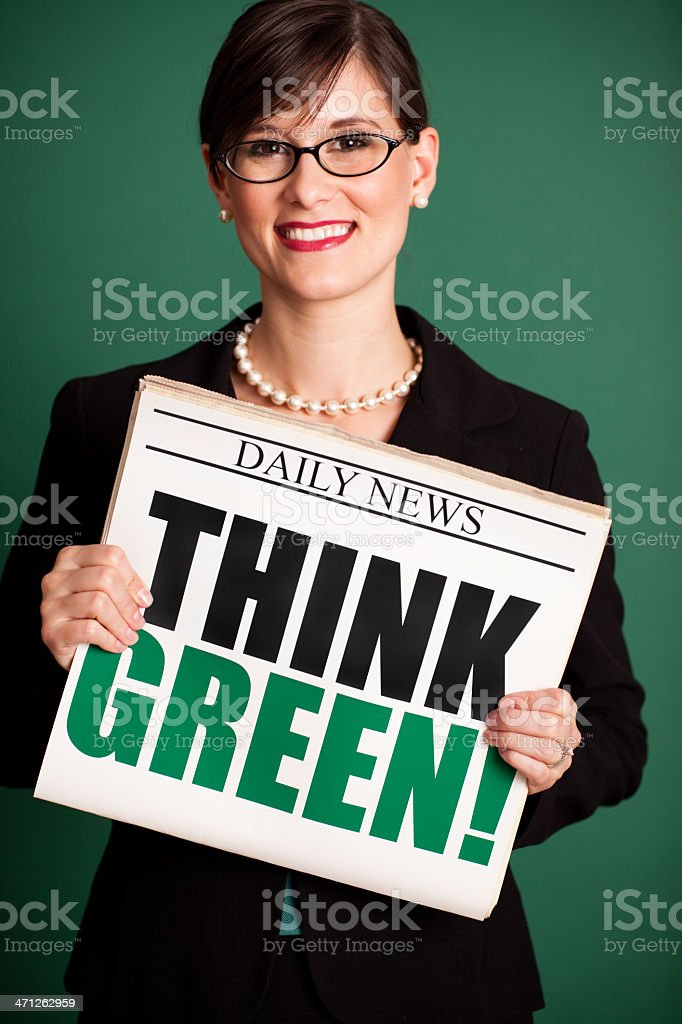 Happy Young Business Woman Holding Newspaper Headlined 'Think Green!' royalty-free stock photo