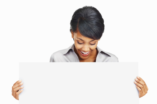 Portrait of a happy business woman looking at a blank board against white