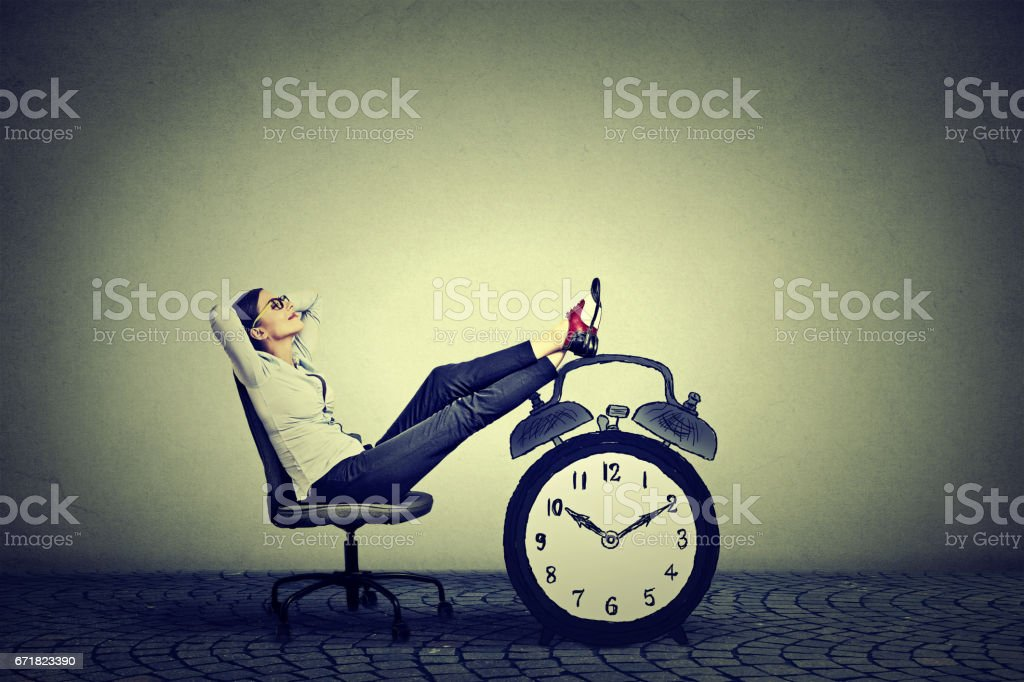 Happy young business woman relaxing sitting in her office. Stress free time management concept stock photo