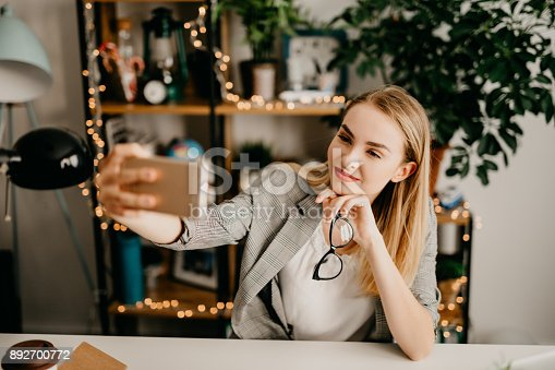 1031394390istockphoto Happy young business woman using phone to make a selfie 892700772