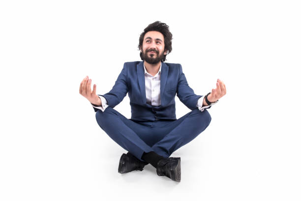 Happy young businessman doing yoga by sitting in lotus position over a white background stock photo