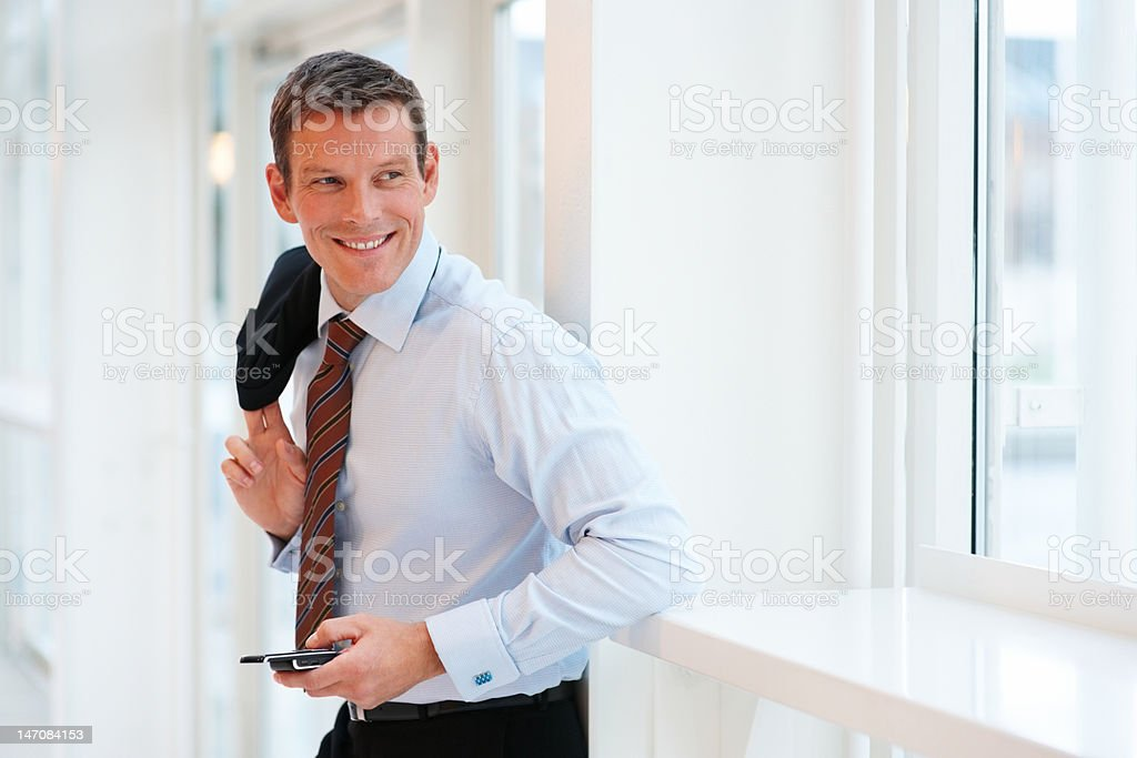 Happy young businessman holding a cellphone royalty-free stock photo