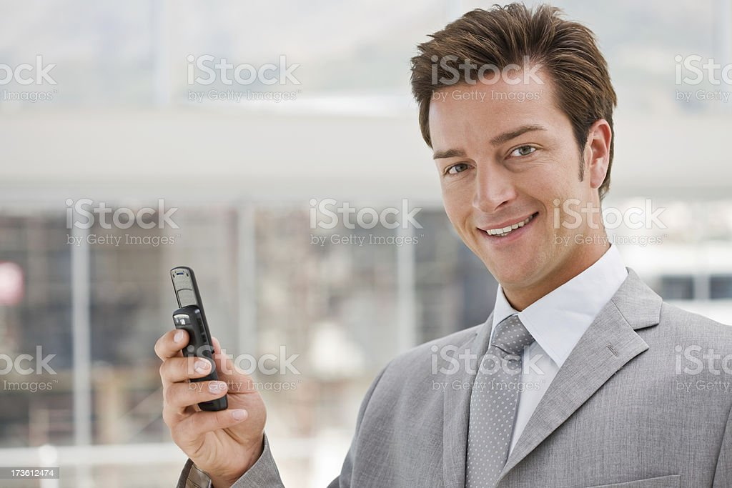 Happy young businessman holding mobile phone royalty-free stock photo