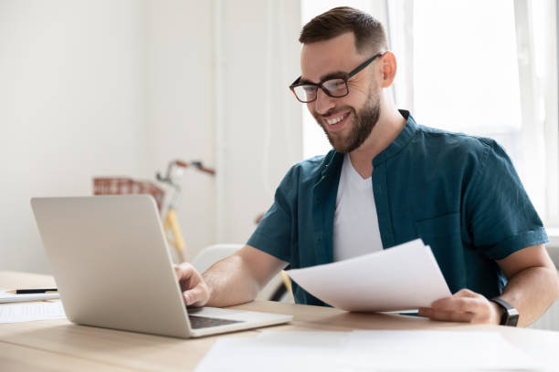 Happy young businessman in eyeglasses working on computer. stock photo