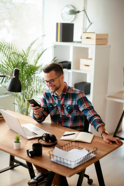 Glücklicher junger Geschäftsmann im Amt. Stockfoto – Foto