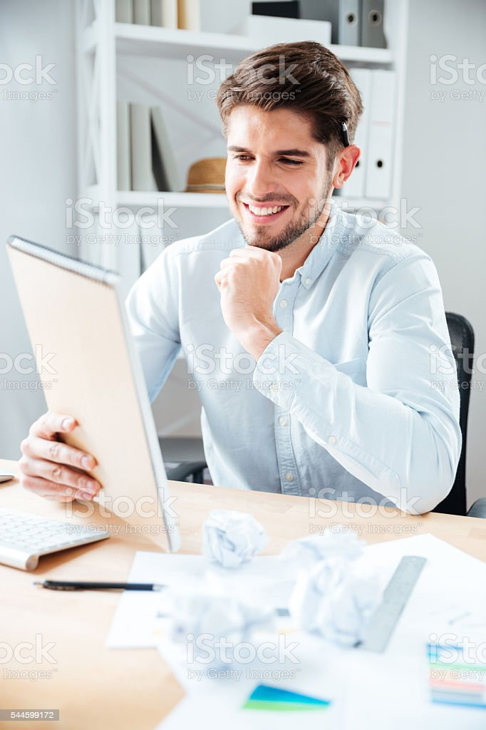 Happy young businessman reading notes in notpad stock photo