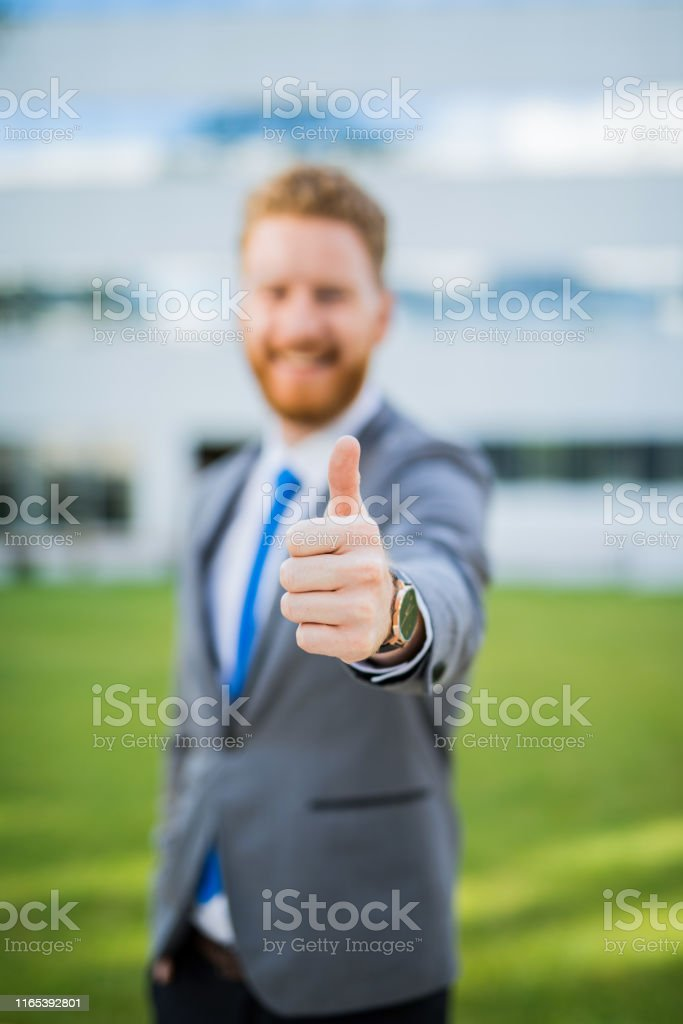Happy young businessman showing thumb up. Focus on foreground.