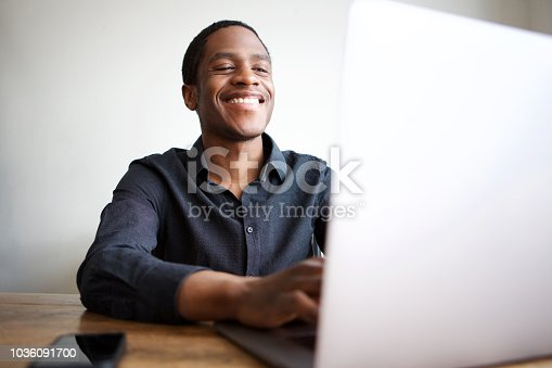 istock happy young businessman sitting at desk with laptop computer 1036091700