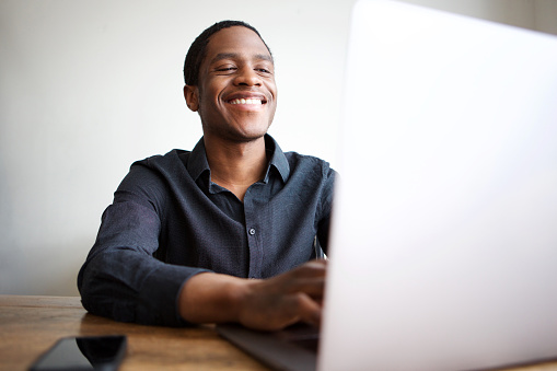 905545264 istock photo happy young businessman sitting at desk with laptop computer 1036091700