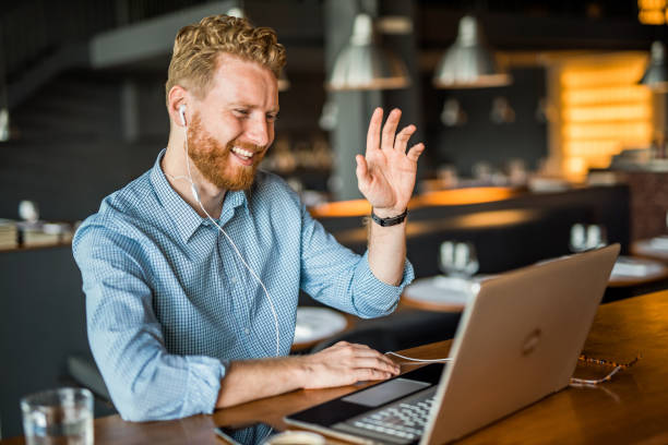 Happy young businessman waving to an online client. stock photo