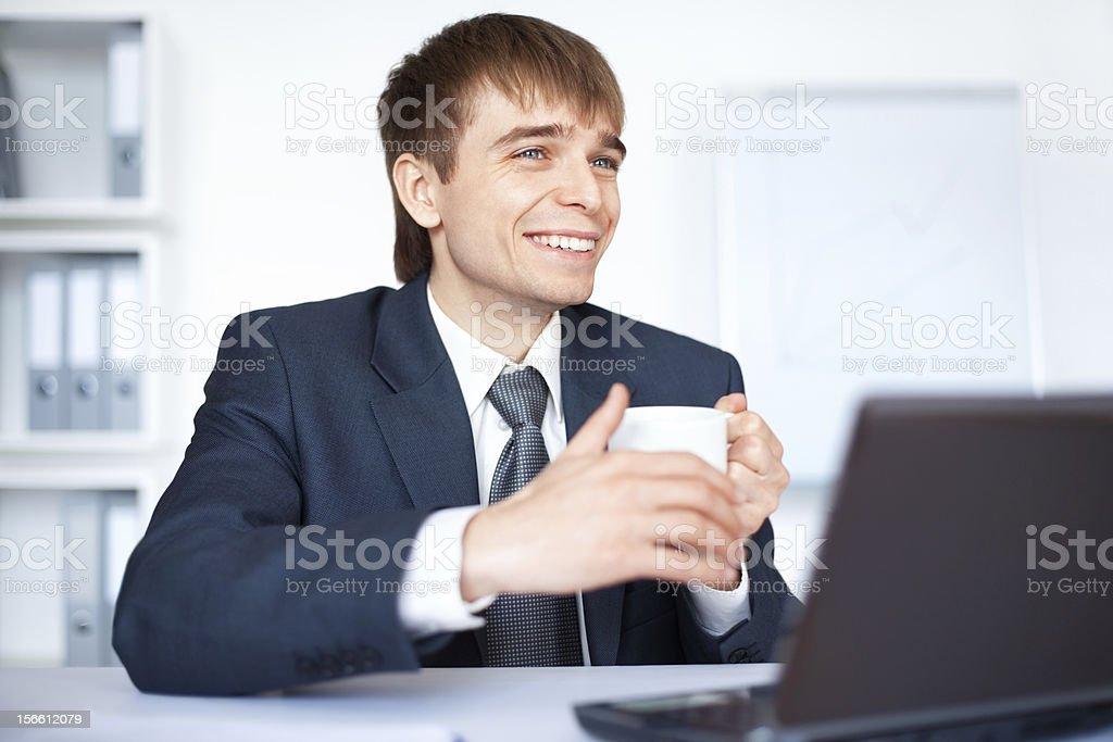 Glückliche junge Geschäftsmann mit einer Tasse Kaffee im Büro – Foto