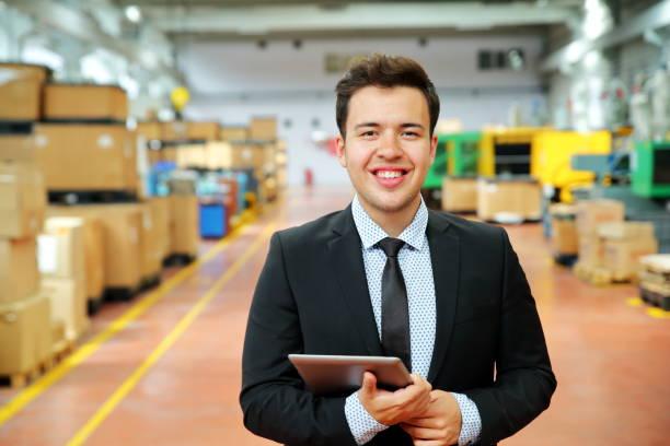 Glücklicher junger Geschäftsmann mit digitalem Tablet in Fabrik – Foto