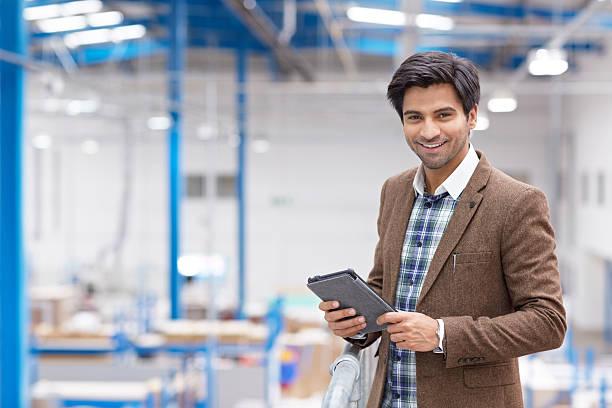 Feliz jovem empresário com tablet digital em armazém - foto de acervo