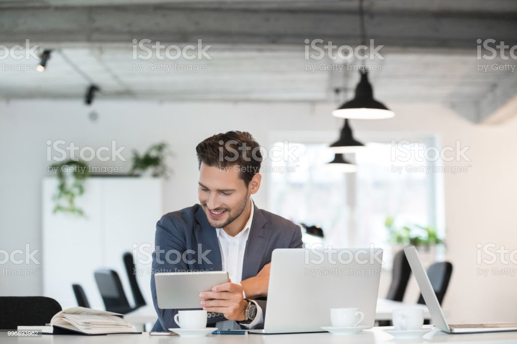 Happy young businessman working in office Smiling young businessman sitting at table with laptop, digital tablet and a book 25-29 Years Stock Photo