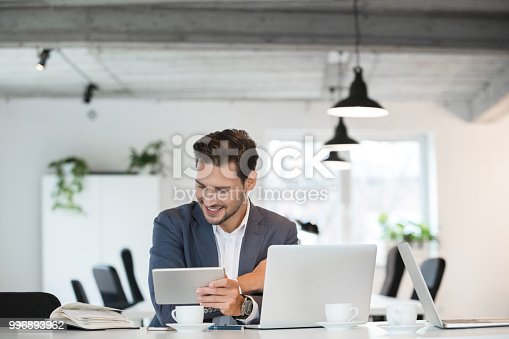 Smiling young businessman sitting at table with laptop, digital tablet and a book