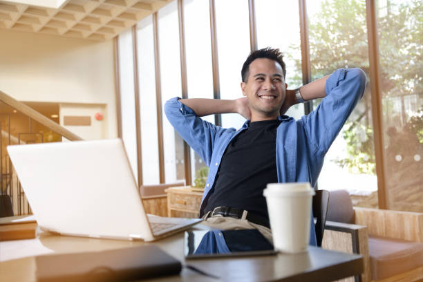 Happy young businessman working on laptop while sitting at his working place in office Happy young businessman working on laptop while sitting at his working place in office asian man in the office stock pictures, royalty-free photos & images