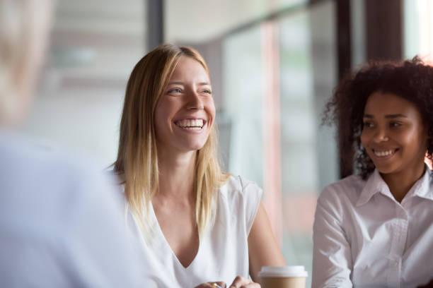 glückliche junge geschäftsfrau trainer mentor führer lacht bei gruppensitzung - mitarbeiterengagement stock-fotos und bilder