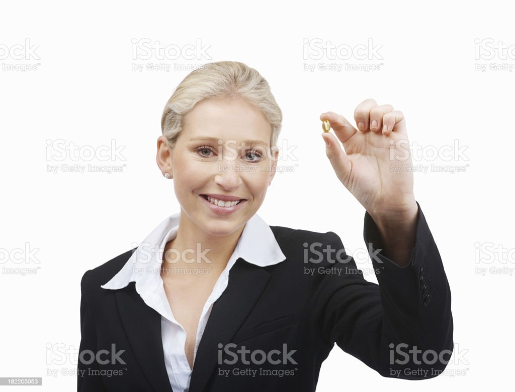 Happy young businesswoman holding a pill royalty-free stock photo