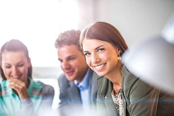 Happy young businesswoman with colleagues in background at office – Foto
