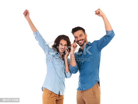 854381780istockphoto happy young casual couple talking on phones celebrating success 854374336