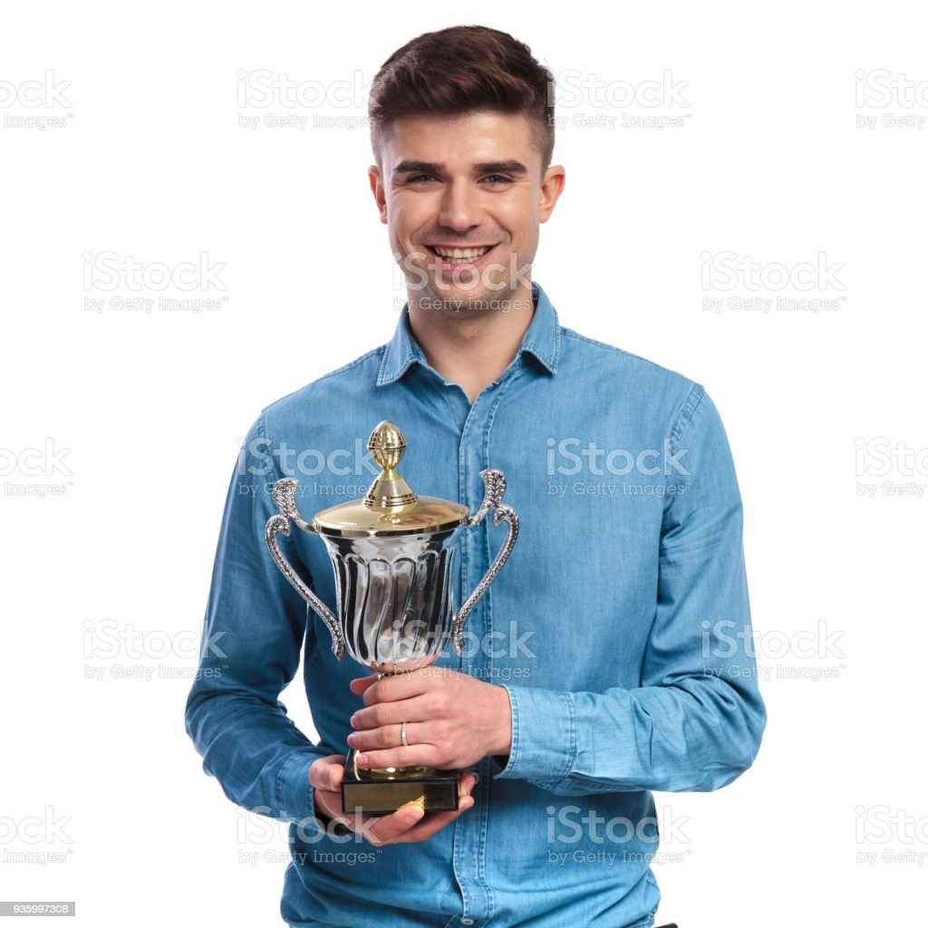 happy young casual man holding his trophy cup award stock photo