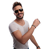 happy young casual man in sunglasses is laughing on white background