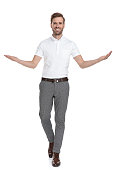 istock happy young casual man walks and welcomes 1131988584