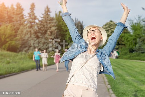 469949126 istock photo Happy young caucasian bald woman in hat and casual clothes enjoying life after surviving breast cancer. Portrait of beautiful hairless girl smiling during walk at city park after curing disease 1163811830